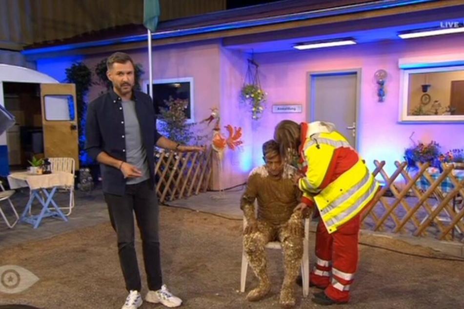 """Jochen Schropp moderierte neben dem mit Schlamm getränkten und sichtlich beeinträchtigten Almklausi weiter. Der """"Mama Laudaaa""""-Sänger wurde danach in eine Klinik gebracht."""