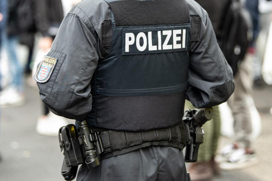 """Ein Polizist steht bei einer Razzia im Kasseler Problemviertel um Platz """"Am Stern"""" vor Passanten."""