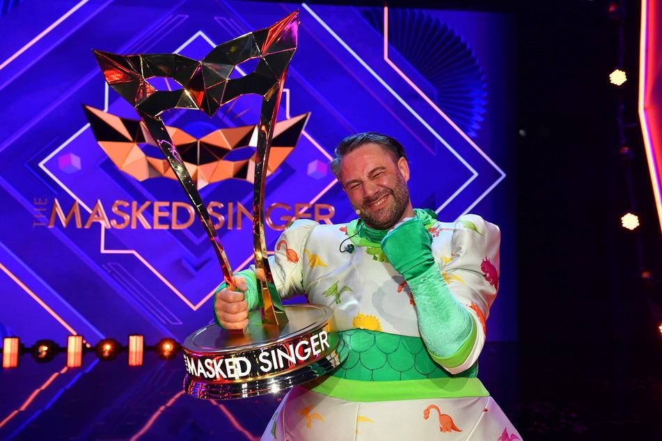 """Sänger Sasha (49) gewann die Frühjahrs-Staffel von """"The Masked Singer"""". Er sang sich in einem Dino-Kostüm mit Zahnspange in die Herzen der Zuschauer."""