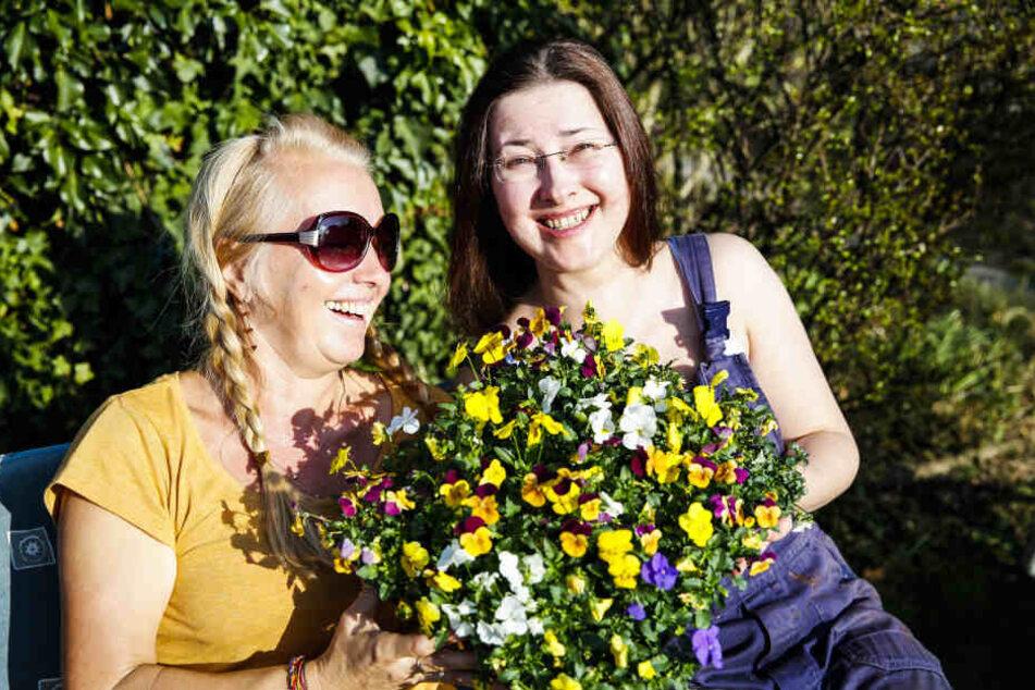 Kerstin (54) und Nele (39) genießen im Garten die Frühlingssonne und erfreuen sich an bunten Horn-Veilchen.