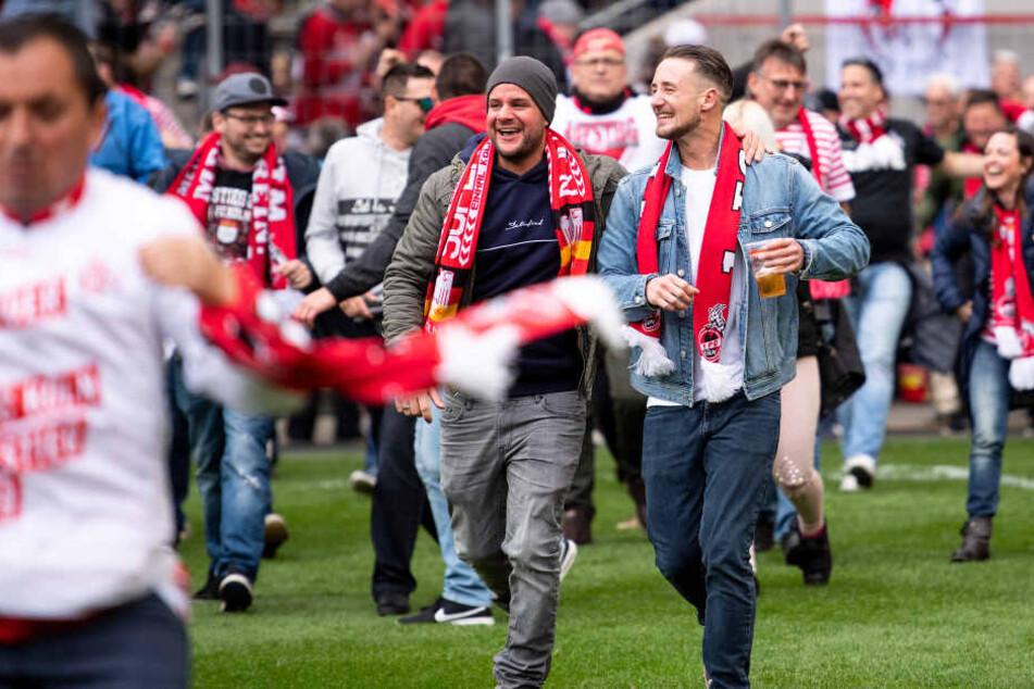 Kölner Fans stürmen den Platz und feiern den Aufstieg ihrer Mannschaft.