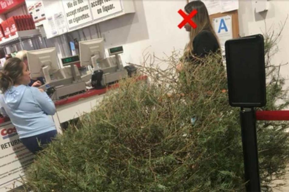 Die Frau steht mit dem vertrockneten Weihnachtsbaum am Serviceschalter.