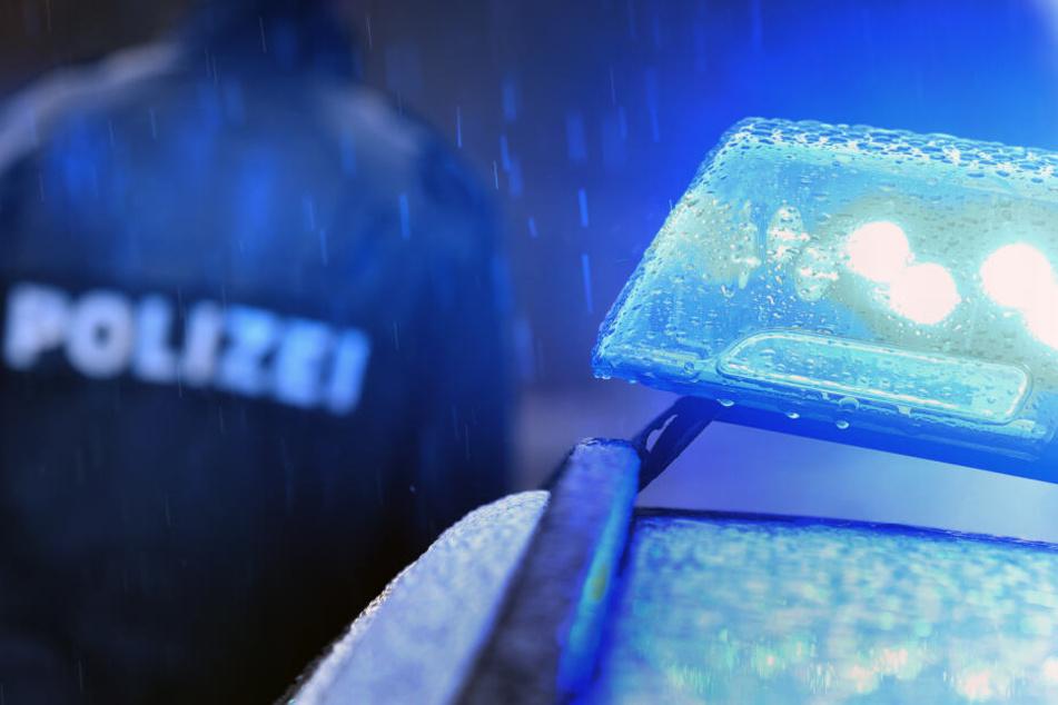 Ein Polizist steht im Regen vor einem Streifenwagen dessen Blaulicht leuchtet (Symbolbild).