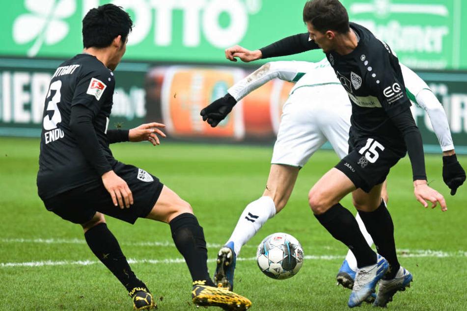 Fürths Branimir Hrgota (M) kämpft mit Stuttgarts Pascal Stenzel (r) und Wataru Endo (l) um den Ball.