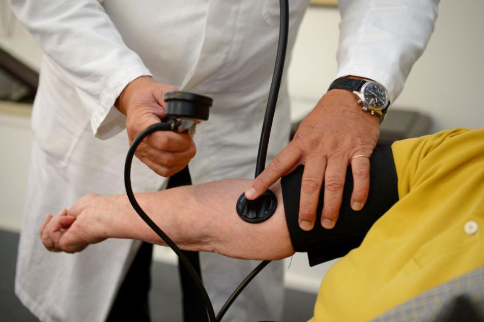 Ein Hausarzt misst in seiner Praxis einer Patientin den Blutdruck. (Symbolbild)