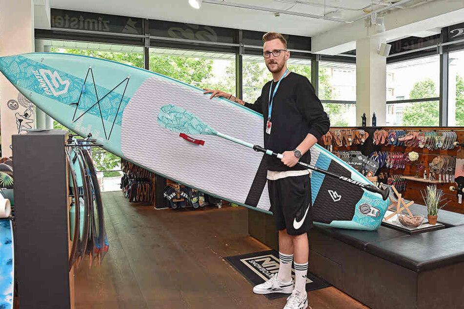 """Für Paddel-Spaß auf der Elbe: """"Planet Sports""""-Verkäufer David Richter (28) mit einem Stand-up-Paddle-Board für 999 Euro (ursprünglich 1270 Euro)."""