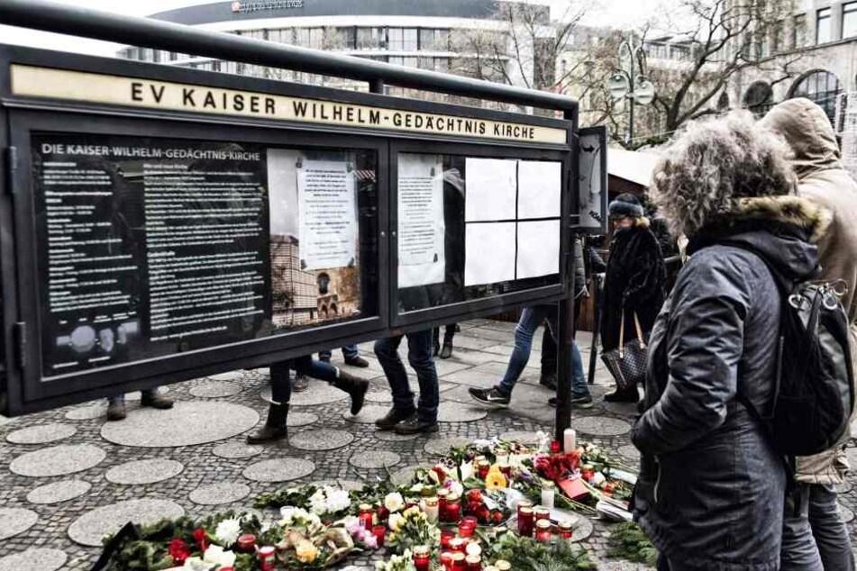 Menschen legen Blumen am Breitscheidplatz in Berlin ab und zünden Kerzen an, um den Opfern zu gedenken.