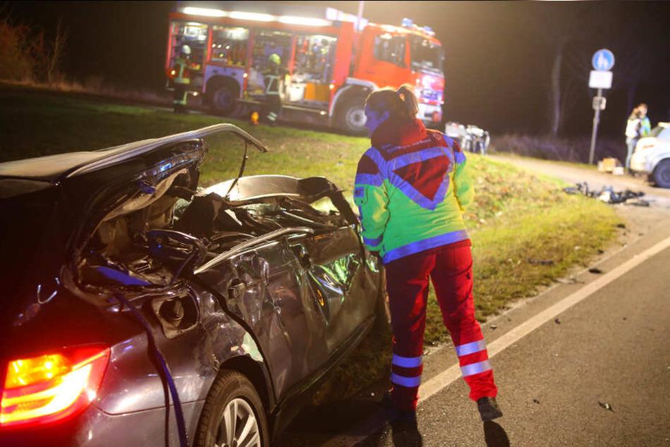 Eine Mitarbeiterin des Rettungsdienstes sieht in eines der Unfallfahrzeuge.