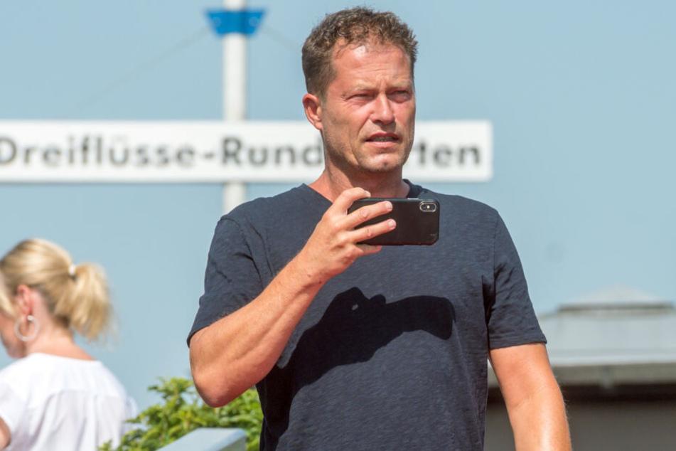 Til Schweiger hält ein Smartphone in der Hand.