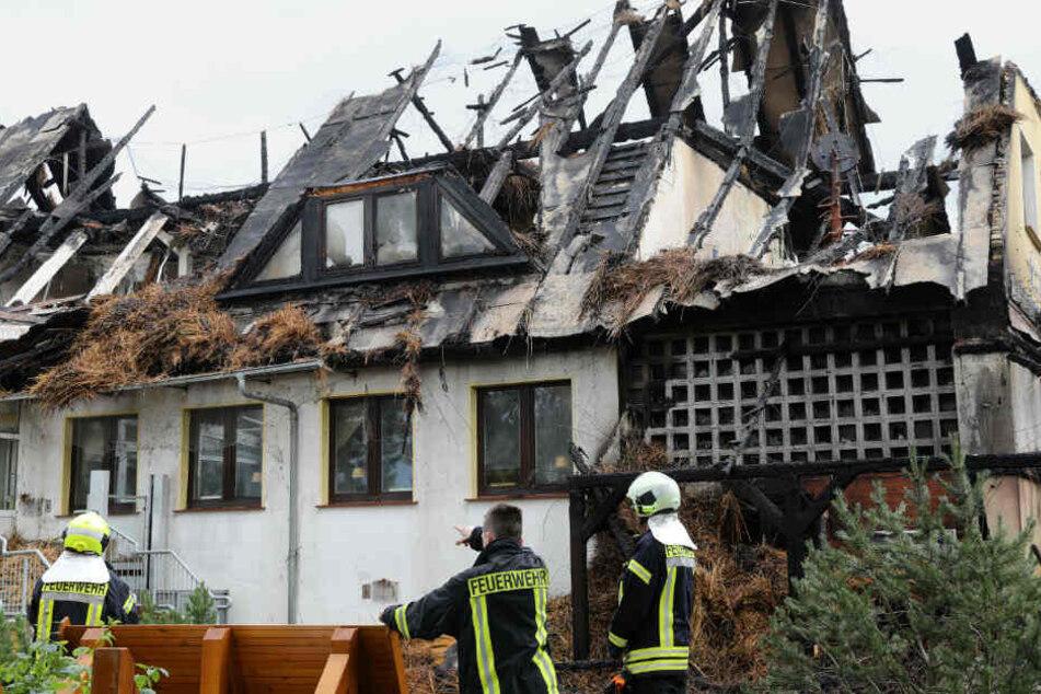 Feuerwehrleute stehen vor dem ausgebrannten Hotel.