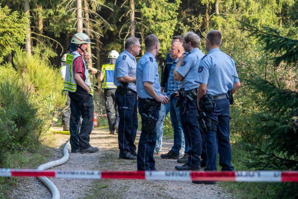 Feuerwehrleute und Polizisten stehen in einem Waldstück auf dem Gebiet von Plettenberg/NRW.