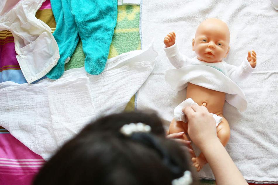 Eine Frau lernt in einer Schulung mit einer Puppe, wie Babys richtig gewickelt werden.