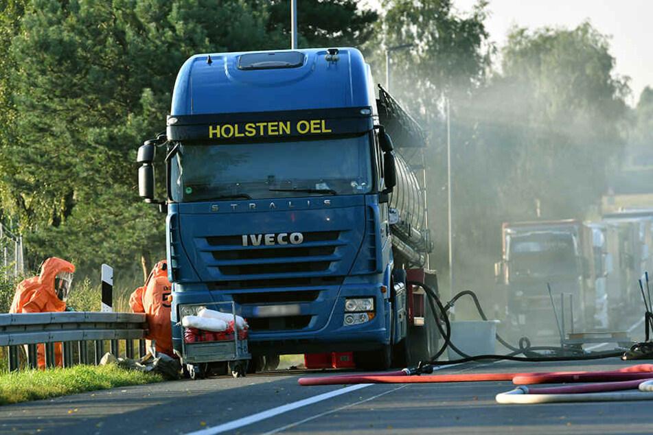 Feuerwehrleute in Schutzanzügen arbeiten am leckgeschlagenen Lkw, der mit 11.000 Liter Salpetersäure beladen war.