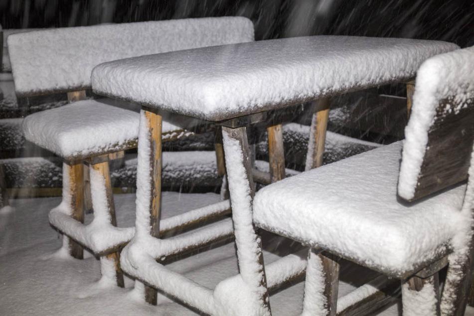 Verschneite Tische und Bänke stehen während eines Wintereinbruchs an der Passstraße bei Grasgehren (Bayern).