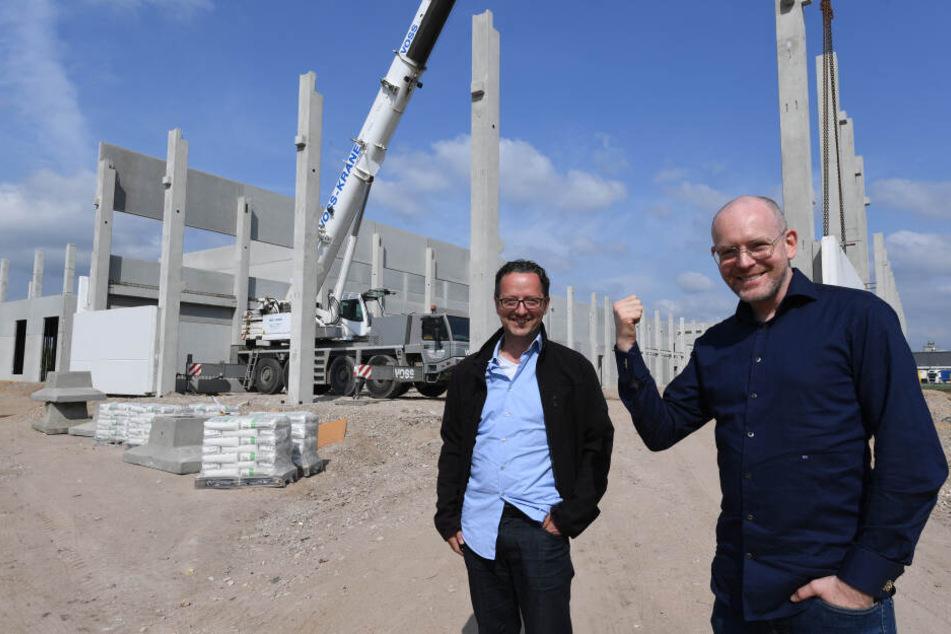 Hendrik Knopp (r), Geschäftsführer des Betreibers Aphria Deutschland GmbH und Thorsten Kolisch, Baustellenleiter, stehen vor dem Rohbau einer Halle.