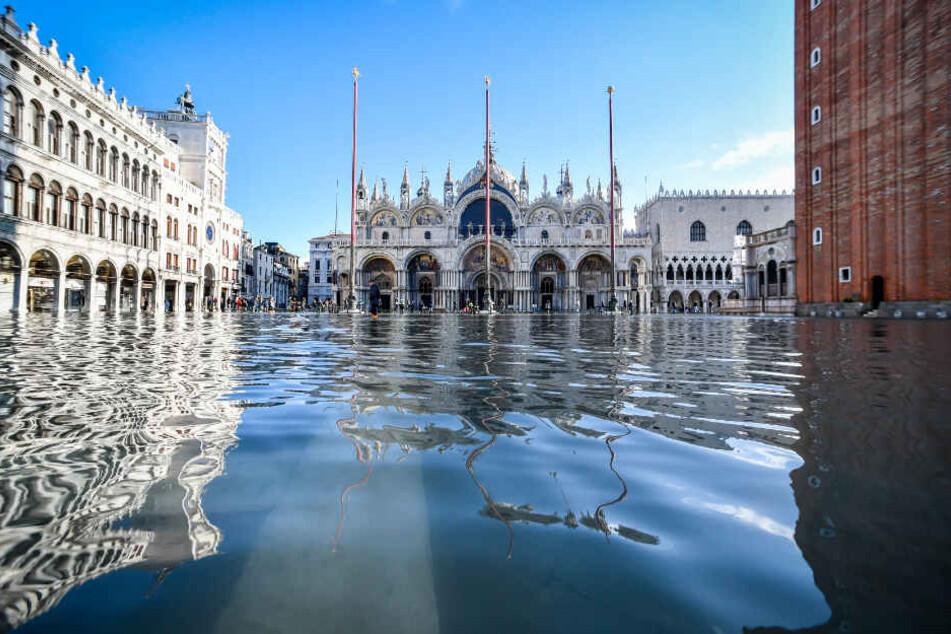Der Dogenpalast spiegelt sich im Hochwasser auf dem Markusplatz. Der italienische Zivilschutz warnte vor neuen Unwettern mit starkem Wind in der Region Venetien.