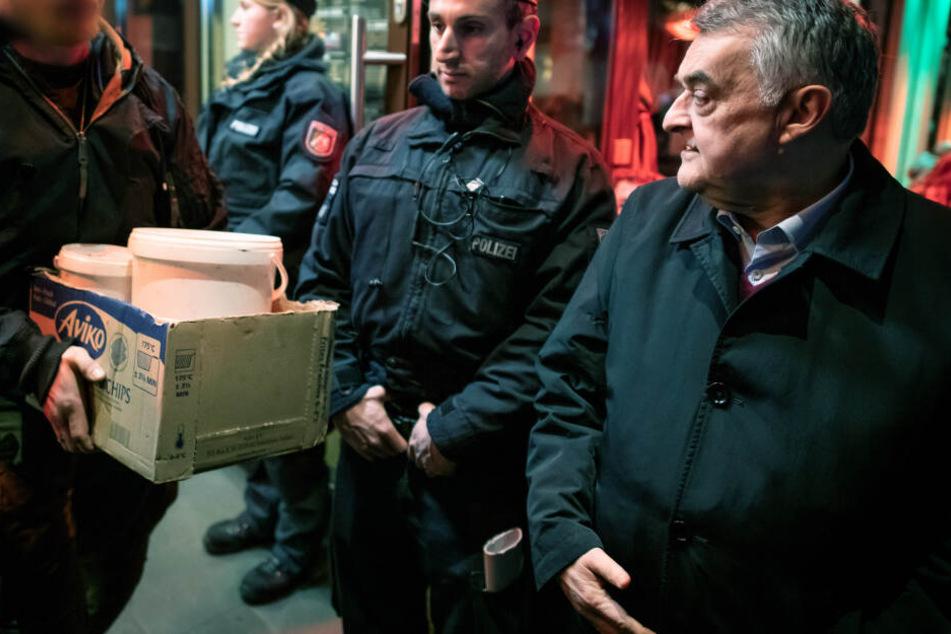 Herbert Reul (CDU, r), NRW-Innenminister, verfolgt, wie nach einer Razzia Beweismittel aus einer Shisha-Bar getragen werden.