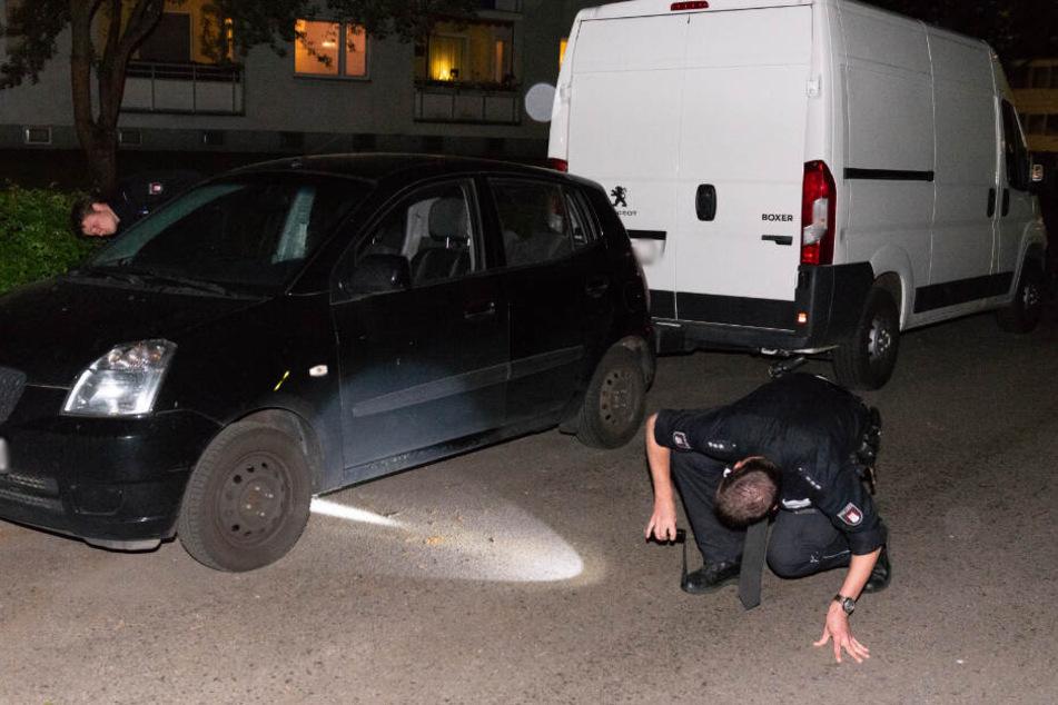 Ein Polizeibeamter sucht mit einer Taschenlampe am Tatort nach Spuren.
