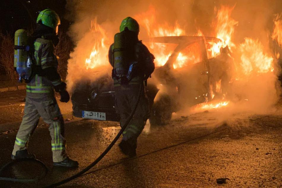 Feuerwehrleute löschen den brennenden Renault in Berlin-Lichtenberg.