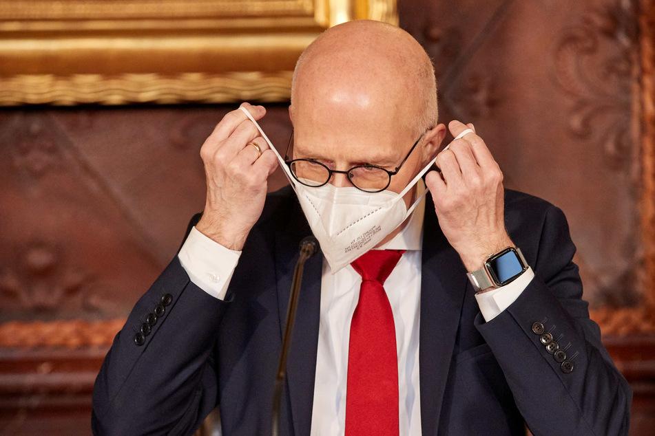 Peter Tschentscher (55, SPD), Erster Bürgermeister von Hamburg, nimmt vor Beginn einer Pressekonferenz im Rathaus seine FFP2-Maske ab. (Archivbild)