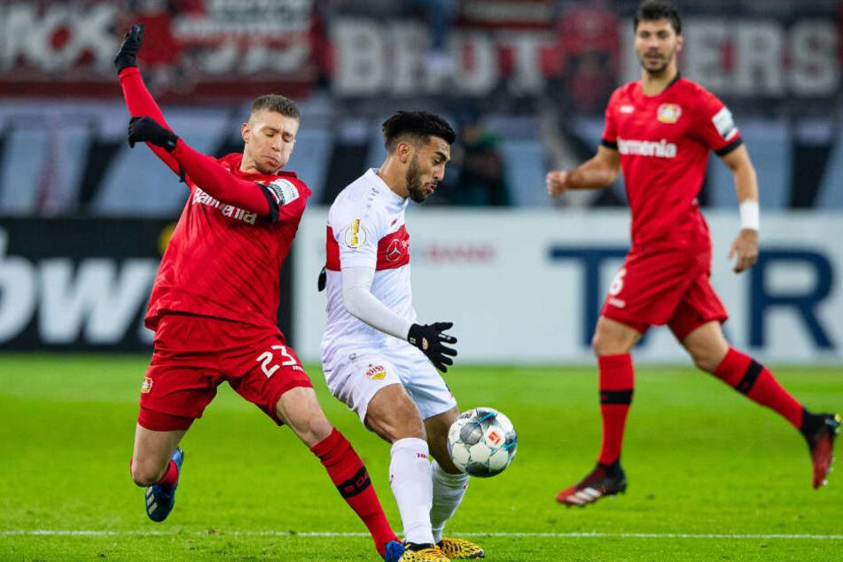 Leverkusens Mitchell Weiser (l) und Stuttgarts Nicolas Gonzalez (M) kämpfen um den Ball.