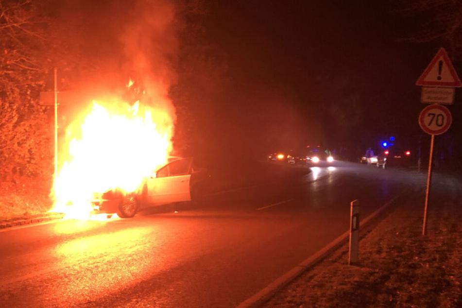 Auf einer Landstraße steht das brennende Fahrzeug.