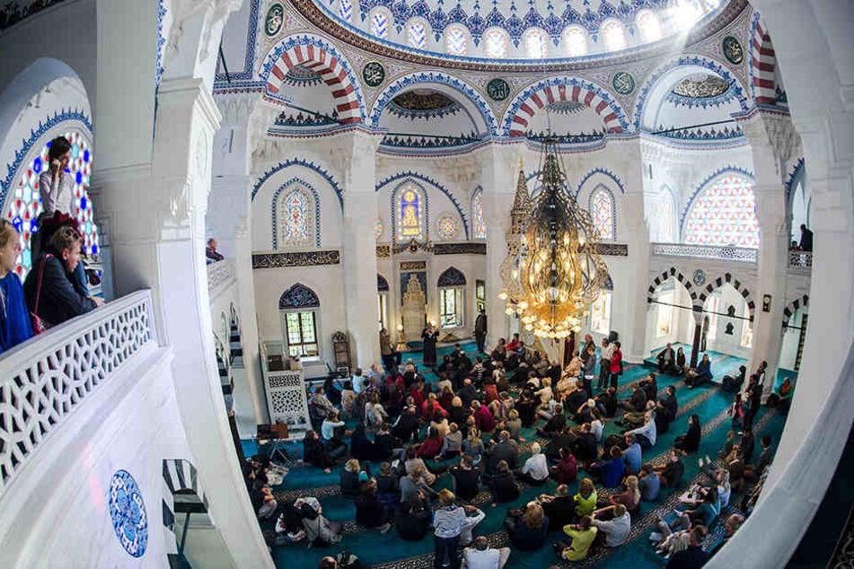 """Zahlreiche Besucher sitzen am 03.10.2015 in Berlin beim bundesweiten """"Tag der offenen Moschee"""" in der Sehitlik-Moschee."""