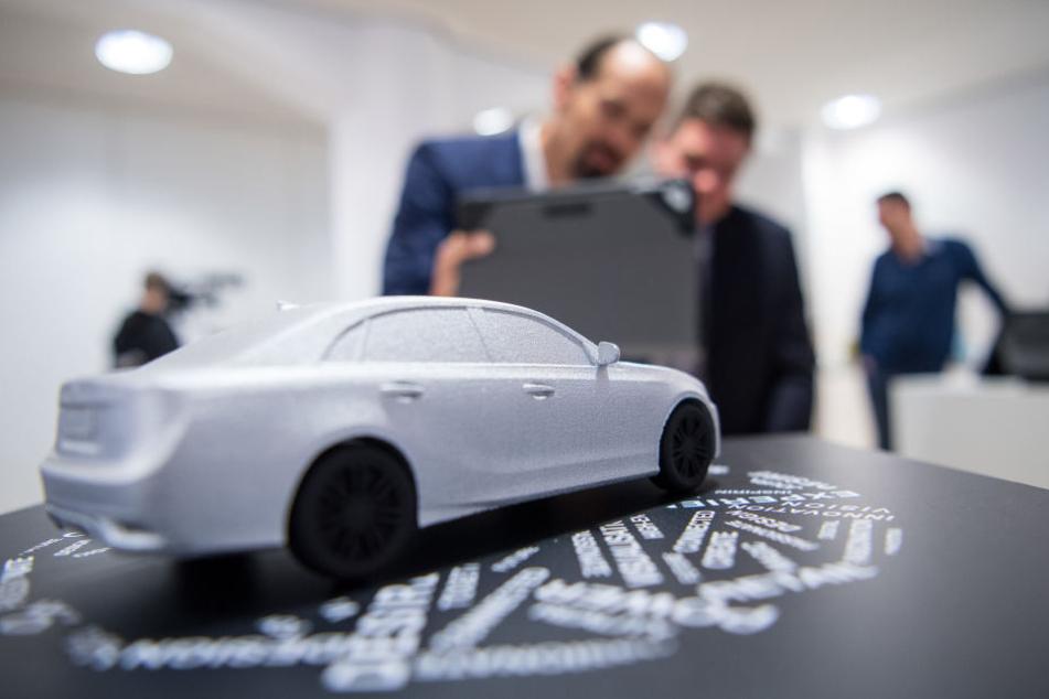 Zwei Männer stehen in Stuttgart vor einem Automodell, das sie mit ihrem Tablet scannen, um sich eine digitale Version anzusehen. (Archivbild)