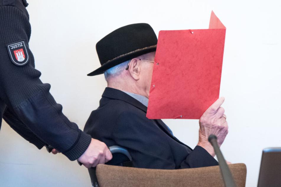 Der angeklagte, ehemalige SS-Wachmann versteckt sein Gericht hinter einer roten Mappe.