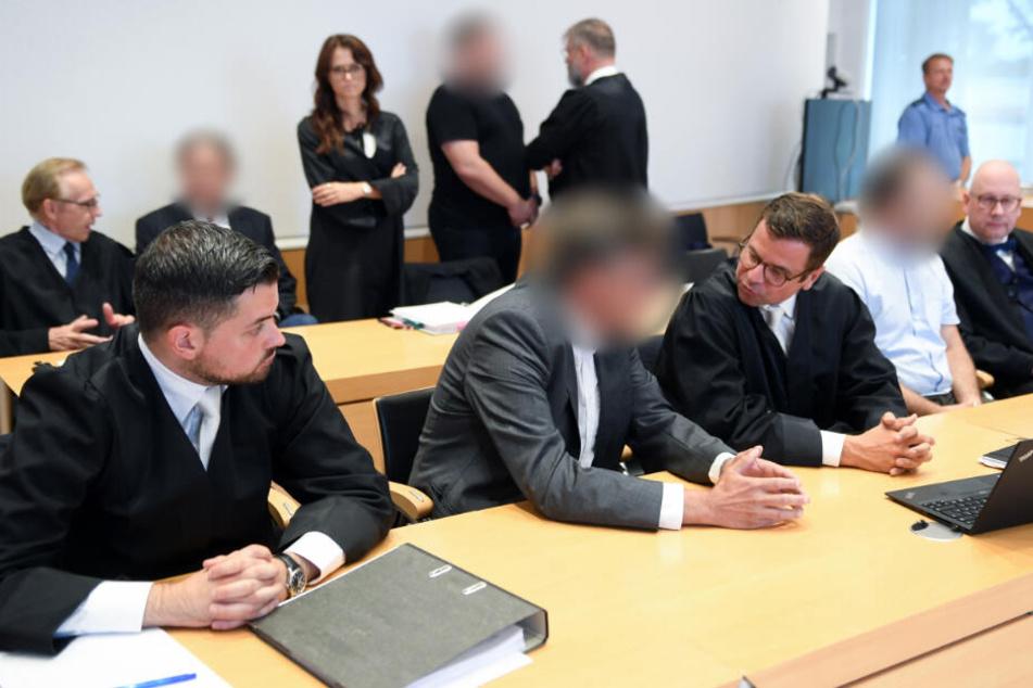 Die vier Angeklagten unterhalten sich zu Beginn des Prozesses am 6.08.2019 im Gerichtssaal des Landgericht Fulda mit ihren Verteidigern.