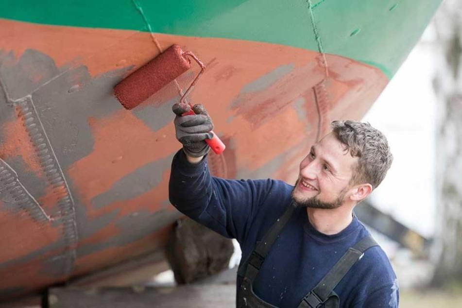 """""""Pillnitz""""-Bootsman Johann Fritz (28) trägt den Schutzanstrich gegen Algen auf die Außenhaut auf."""