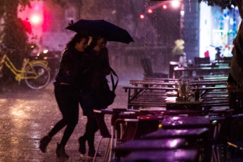 Zwei Frauen flüchten auf der Sternschanze durch starken Regen. (Archivbild)