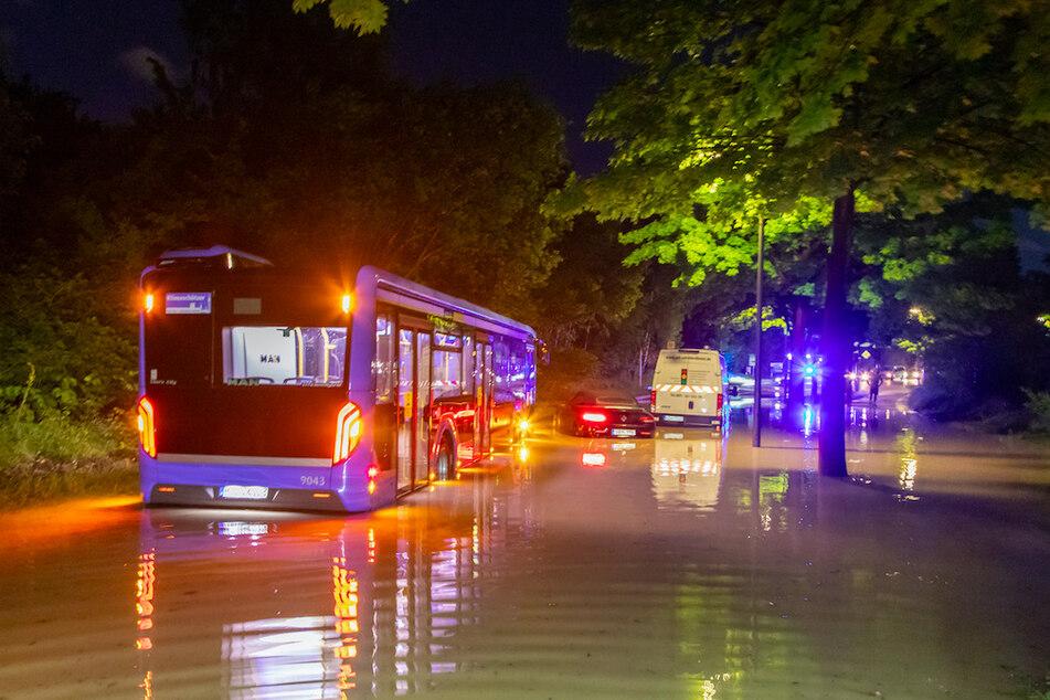 Ein Bus, ein Transporter sowie ein Auto blieben auf einer überfluteten Straße in München stecken.