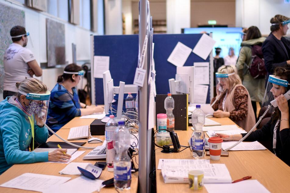 Mitarbeiter des Gesundheitsamtes Berlin-Mitte mit Gesichtsschutzschirm telefonieren im Lagezentrum des Gesundheitsamtes Mitte.