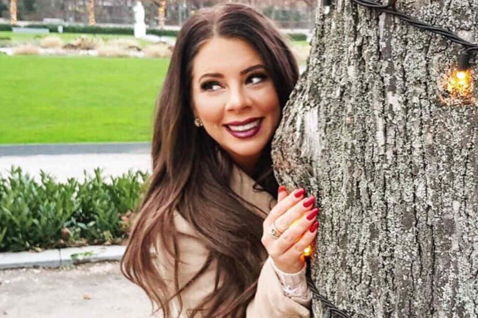 Jenny Frankhauser versteckt sich lächelnd hinter einem Baum.