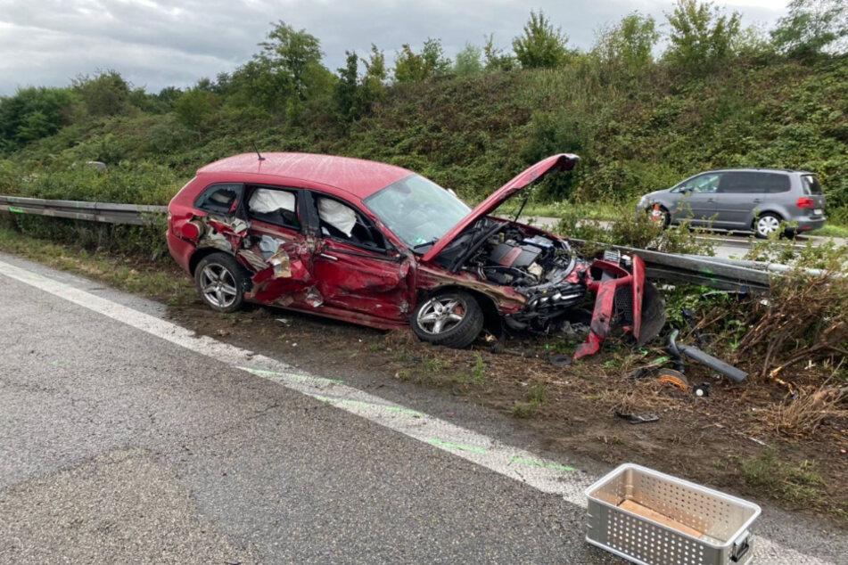 Ein Auto steht stark beschädigt nach dem Unfall an der Leitplanke.
