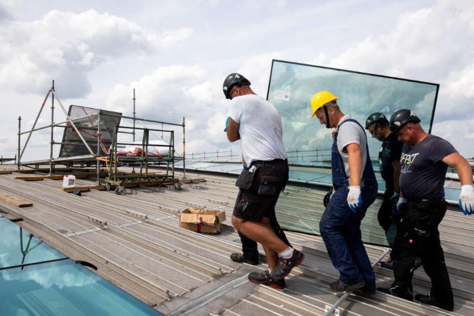 Arbeiter tragen ein neues Glaselement aufs Dach von Terminal 2 am Flughafen Hamburg.