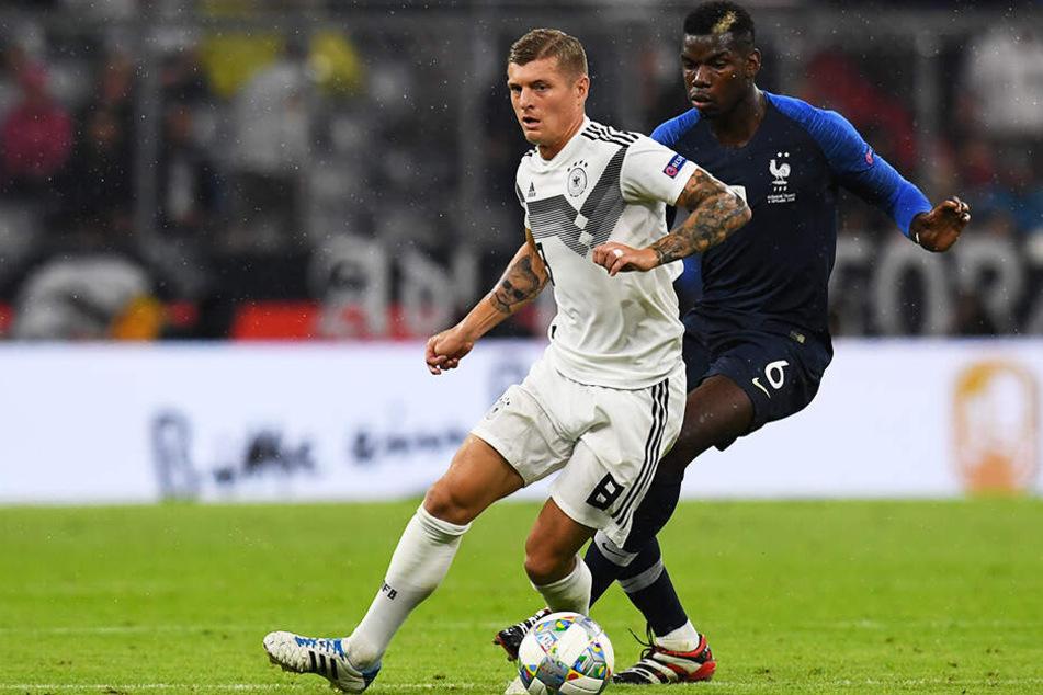 Hier Gegner, bald Teamkollegen? Paul Pogba (r.) versucht, Deutschlands Toni Kroos, der bei Real Madrid spielt, den Ball abzuluchsen.