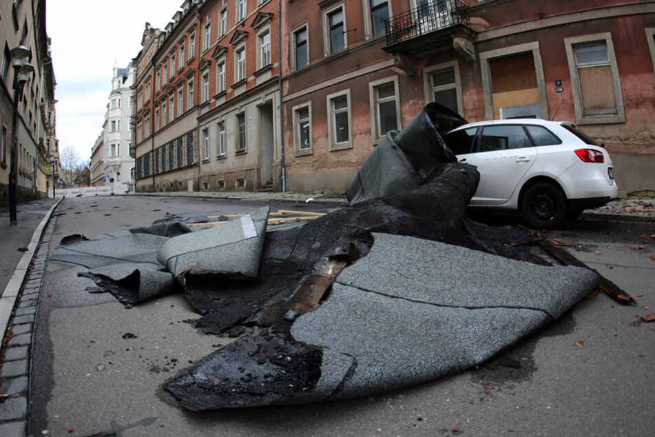 Ein abgerissenes Dach liegt auf einem Auto in Pirna (Sachsen).