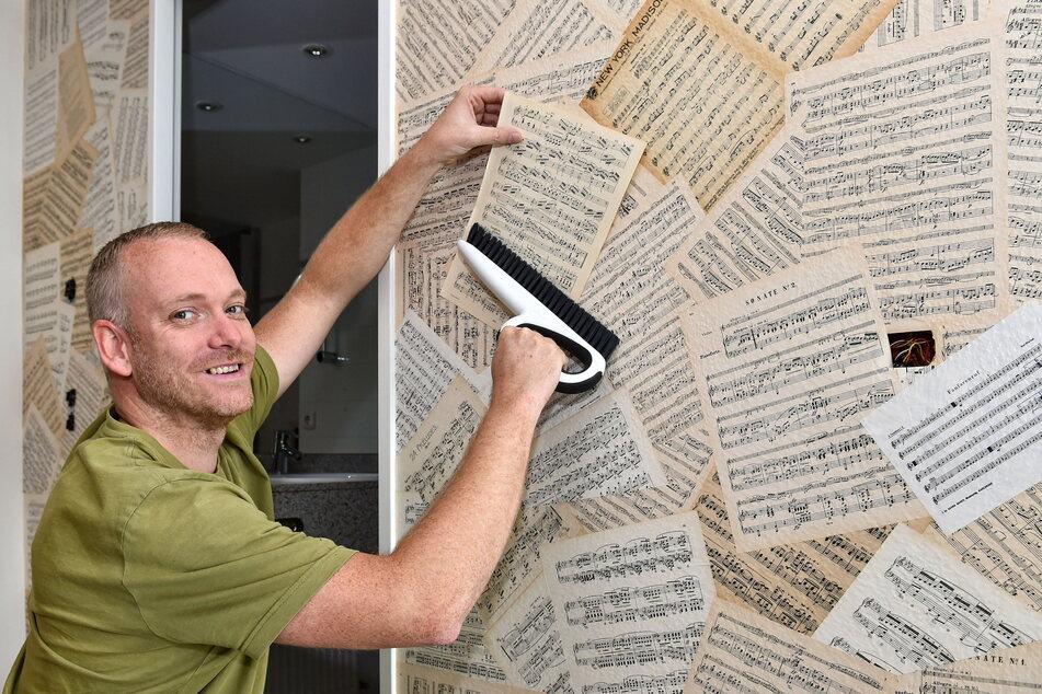 Michael Dietze (40) tapeziert eine Zimmerwand mit alten Notenblättern.