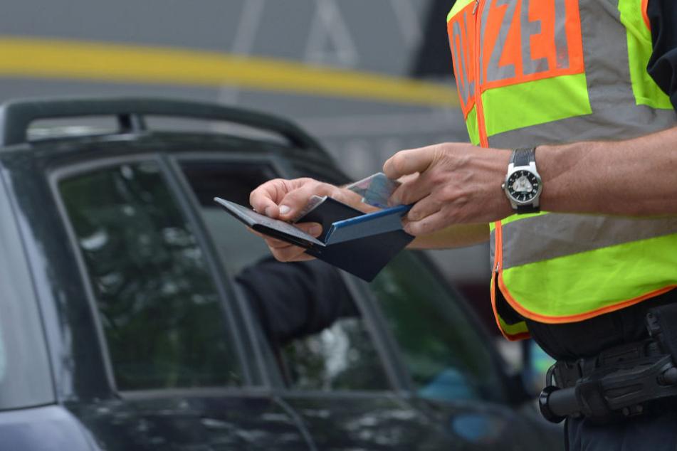 Ein Beamter kontrolliert die Papiere eines Autofahrers. (Symbolbild)