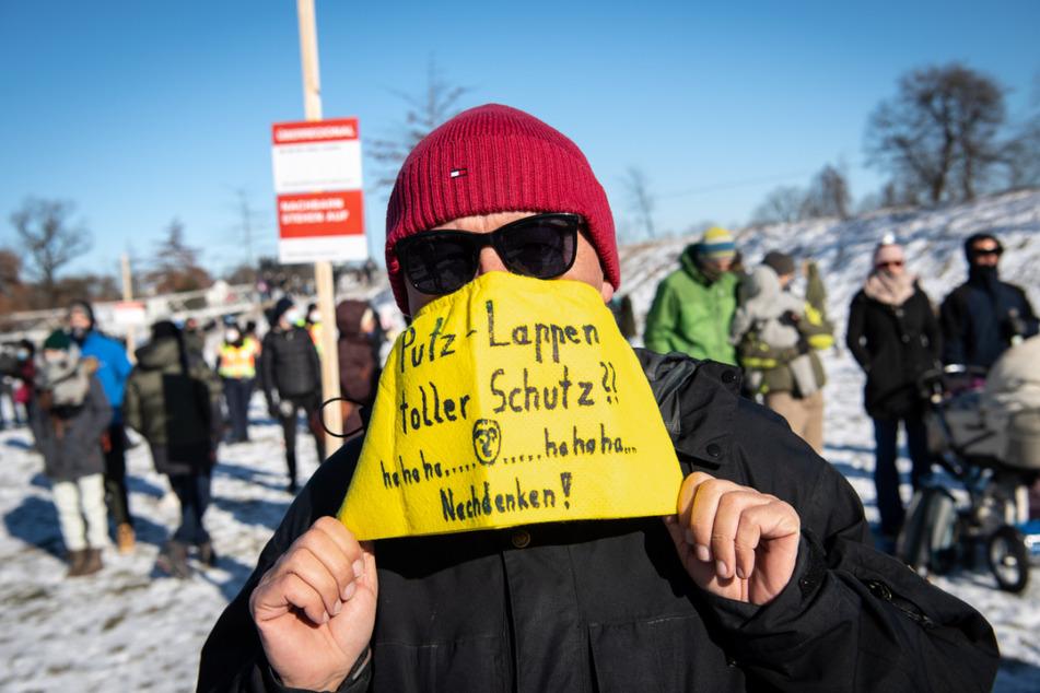 """Ein Demonstrationsteilnehmer trägt einen Lappen mit der Aufschrift """"Putz-Lappen toller Schutz?? hahaha - hahaha - Nachdenken!"""" als Mundschutz."""