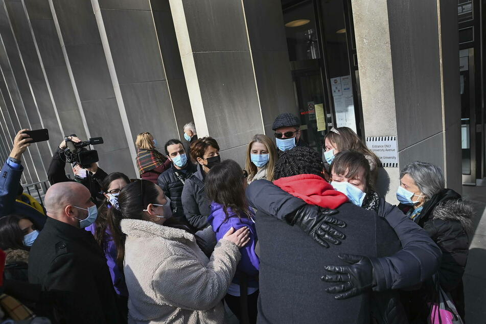 Survivors along with family and friends of survivors and victims share a moment outside the courthouse after the verdict.