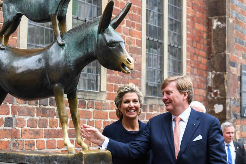 Das niederländisches Königspaar Willem-Alexander und Maxima stehen bei ihrem Bremen-Besuch an der Figur der Bremer Stadtmusikanten.