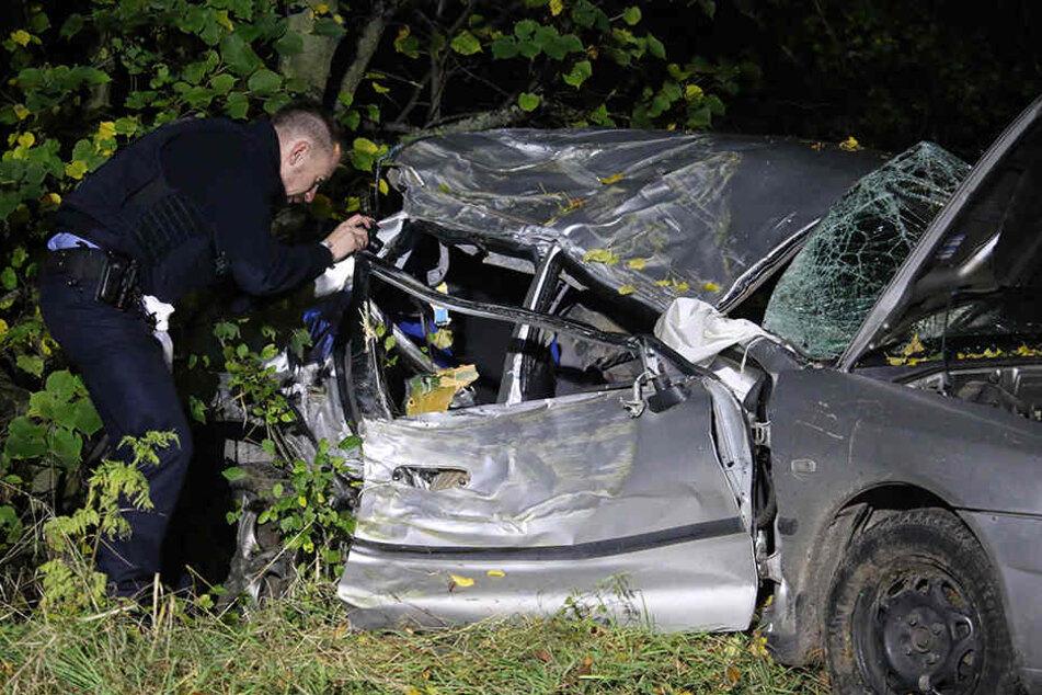 Ein Polizist fotografiert nach dem schrecklichen Unfall das Fahrzeugwrack.
