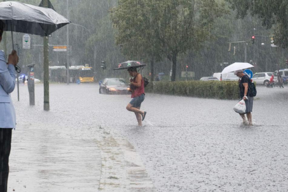 Fußgänger waten am Freitag durch die überflutete Tiergartenstraße in Berlin.