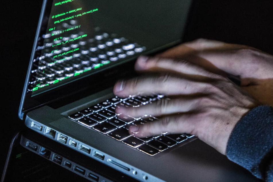 Ein Mann tippt auf einer beleuchteten Tastatur eines Laptops, während auf dem Monitor ein Hacker-Programm geöffnet ist.