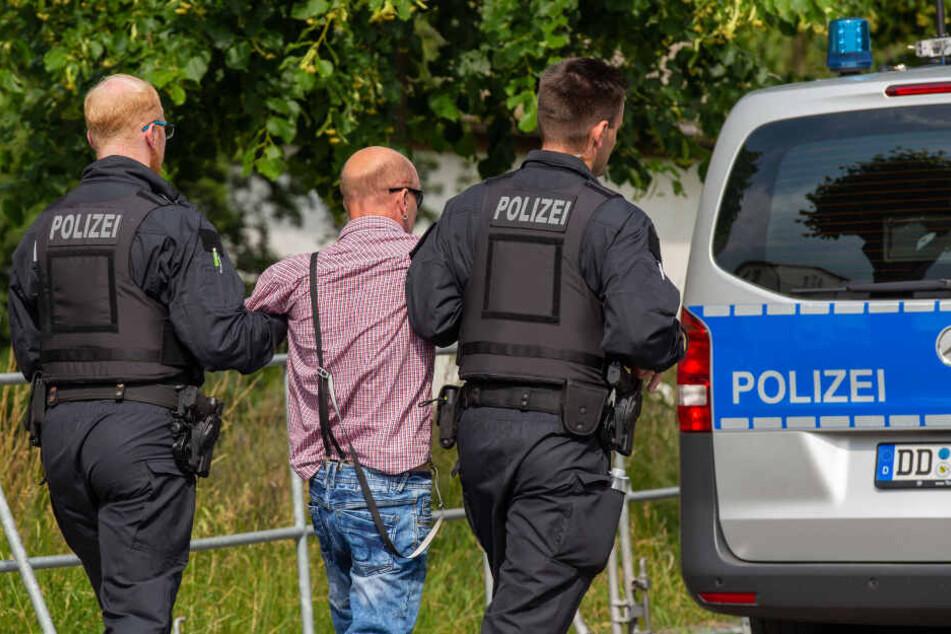 Ein Besucher des Rechtsrockfestivals Schild und Schwert wird von zwei Polizisten mitgenommen, nachdem er einen Journalisten angriffen hat.