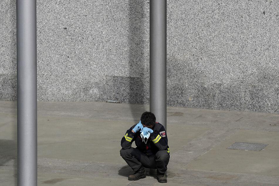 Ein Feuerwehrmann hält seinen Mundschutz in der Hand, während er vor dem provisorischen Lazarett, das auf dem Messegelände Ifema errichtet wurde, telefoniert.