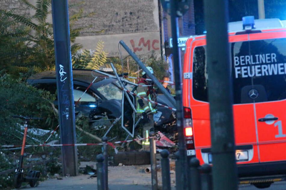 Ein Feuerwehrmann steht bei dem Unfallwagen.
